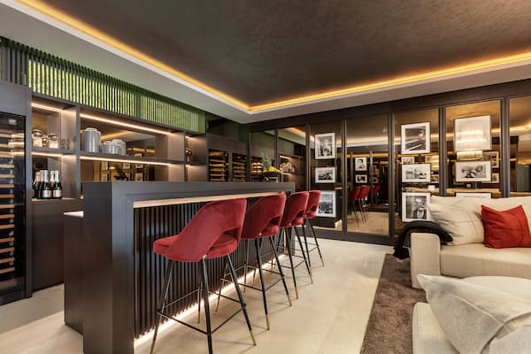 Black bar with red bar chairs and beautiful lights - Original Interiors