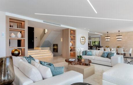 Living room white with wooden cabinets and orchids white couch sofas - Original Interiors