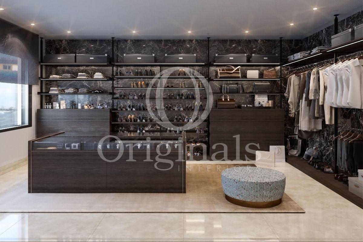 A large walk in closet with black shelves and a beige hard floor - Originals Interiors