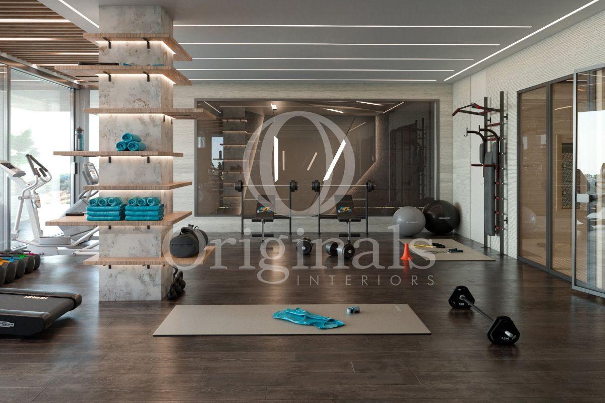 Gym area with dark wooden floor, a large mirror, beige walls and gym equipment - Originals Interiors