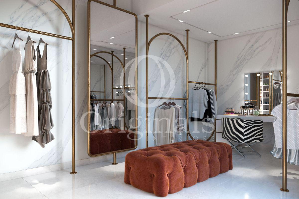 Large closet with marble walls, golden accents and a red pouf - Originals Interiors