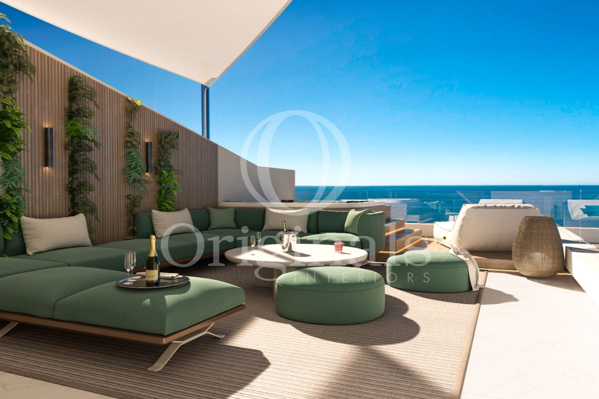 Outside lounge area with green sofa, brown carpet and wooden wall with hanging plants and sea view - Originals Interiors