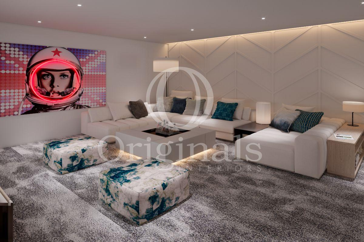 A lounge area with a large white sofa, grey fluffy carpet, flower printed poufs and an artwork on the wall - Originals Interiors