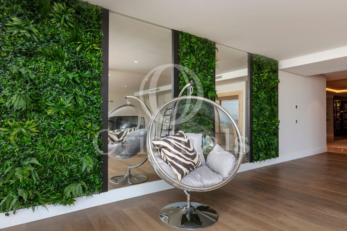 Wall with living plant backgrounds, mirrors and a hanging chair - Originals Interiors