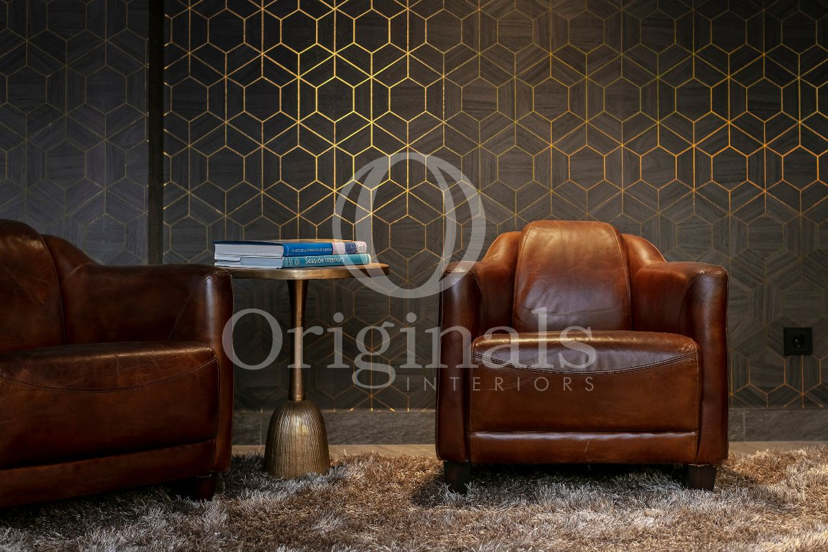 Reading area with brown leather chairs and black walls with golden accents - Originals Interiors