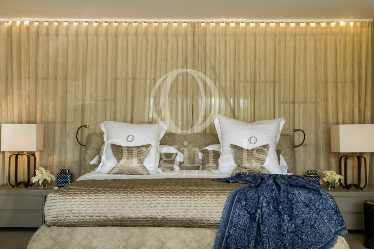 Bedroom with beige-golden duvet, white pillows and a beige-golden curtain - Originals Interiors