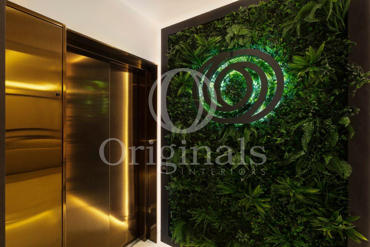 Golden elevator with a living plant background - Originals Interiors