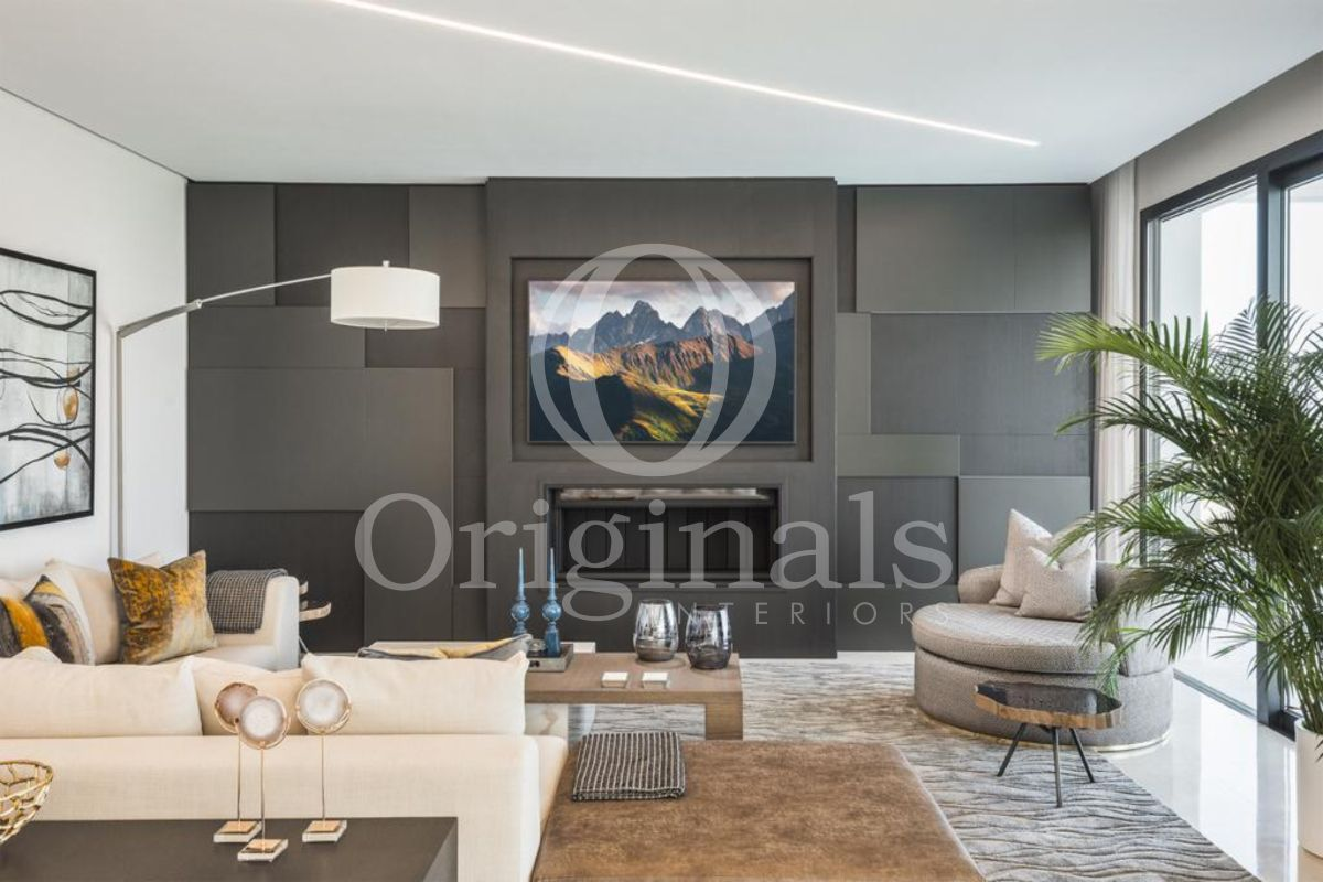 Living room with dark background, beige sofa and grey and brown carpets - Originals Interiors