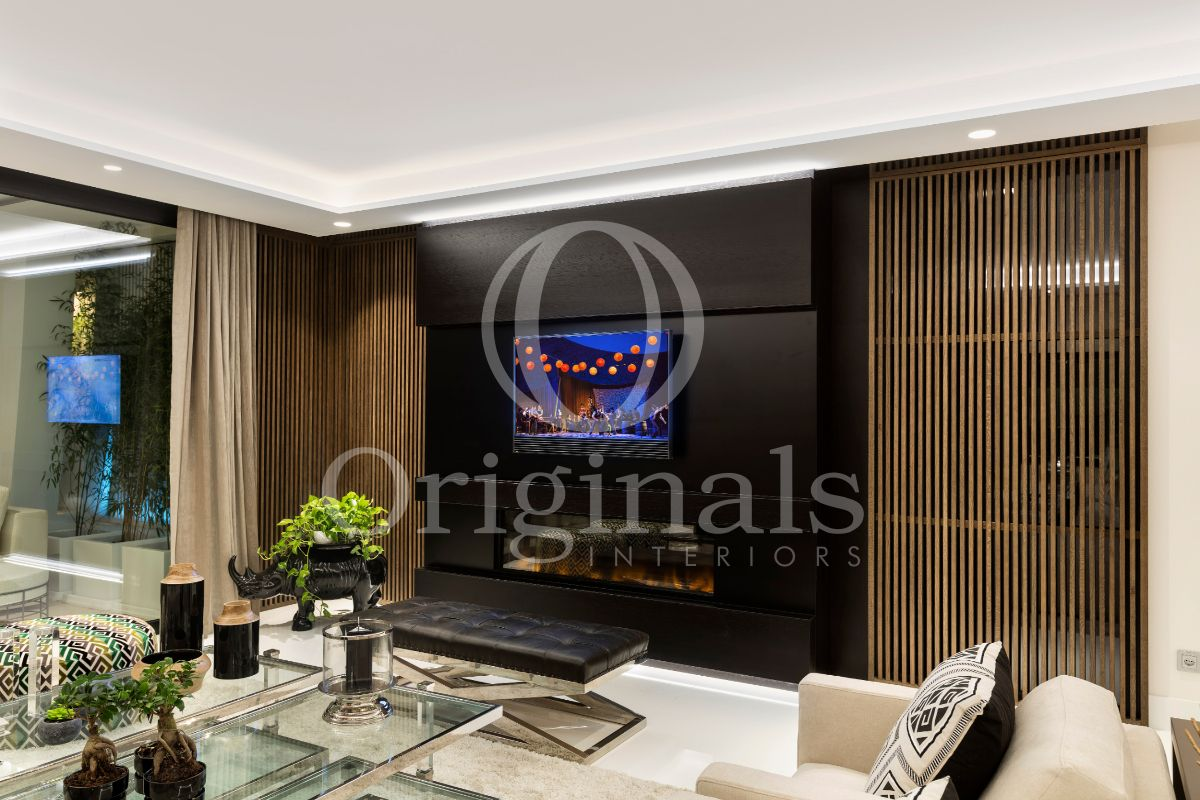 Living room with large black firetpit, wooden accents, white sofa´s and a glass coffee table - Originals Interiors