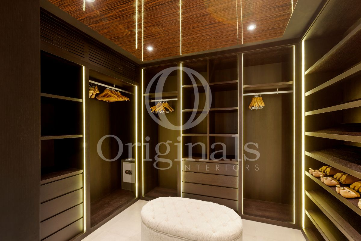 Luxurious walk-in closet made out of dark wood with luxurious lighting - Originals Interiors