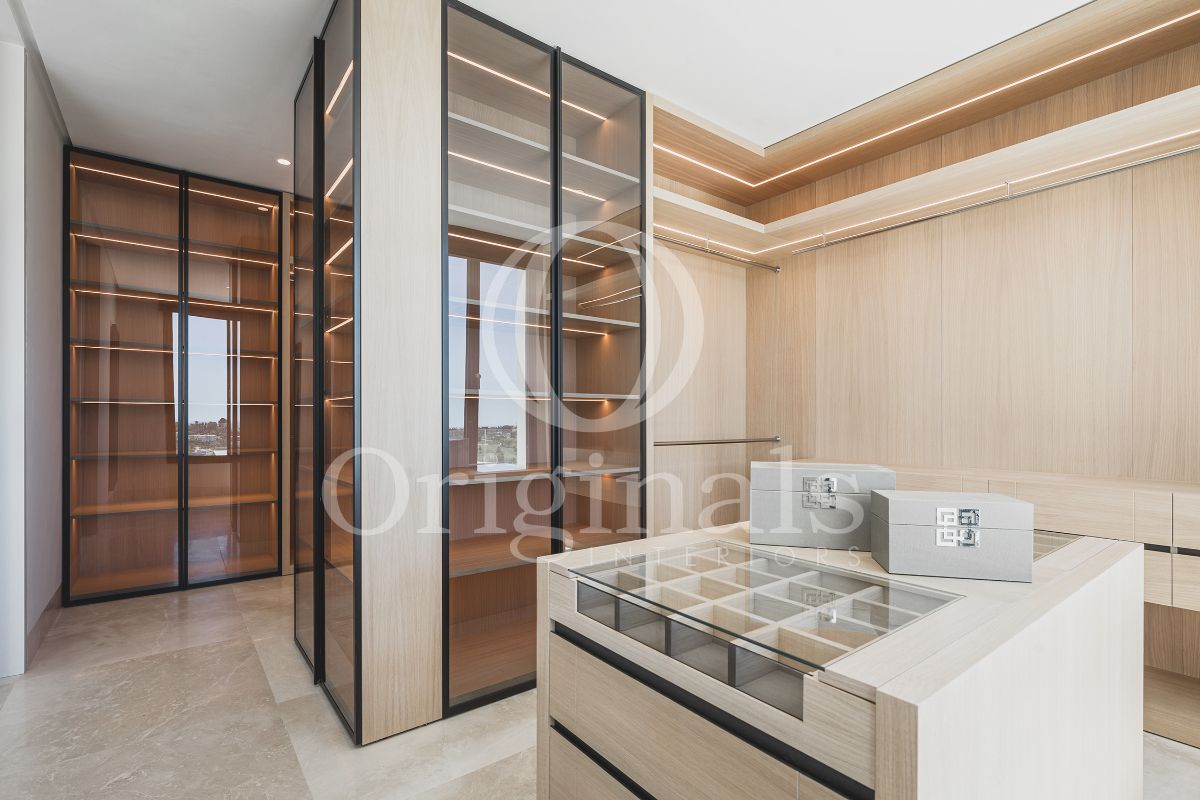 A wooden walk in closet with glass doors and a watch and tie storage - Originals Interiors