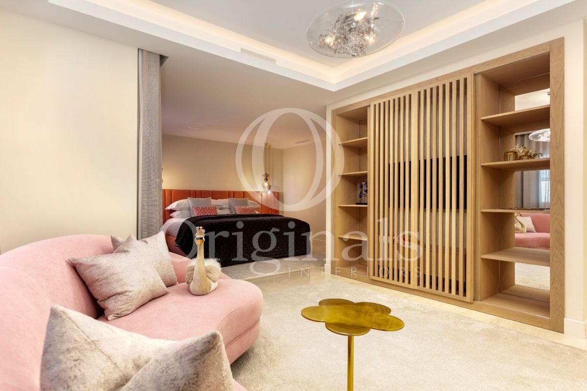 Bedroom with wooden shelf, pink sofa and beige carpet - Originals Interiors