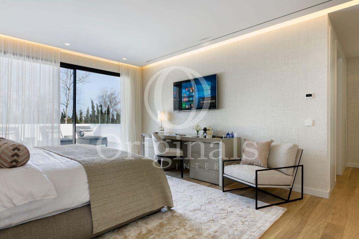 Bedroom with beige wallpaper, roof lighting, luxurious bed and a grey designer shelf - Originals Interiors