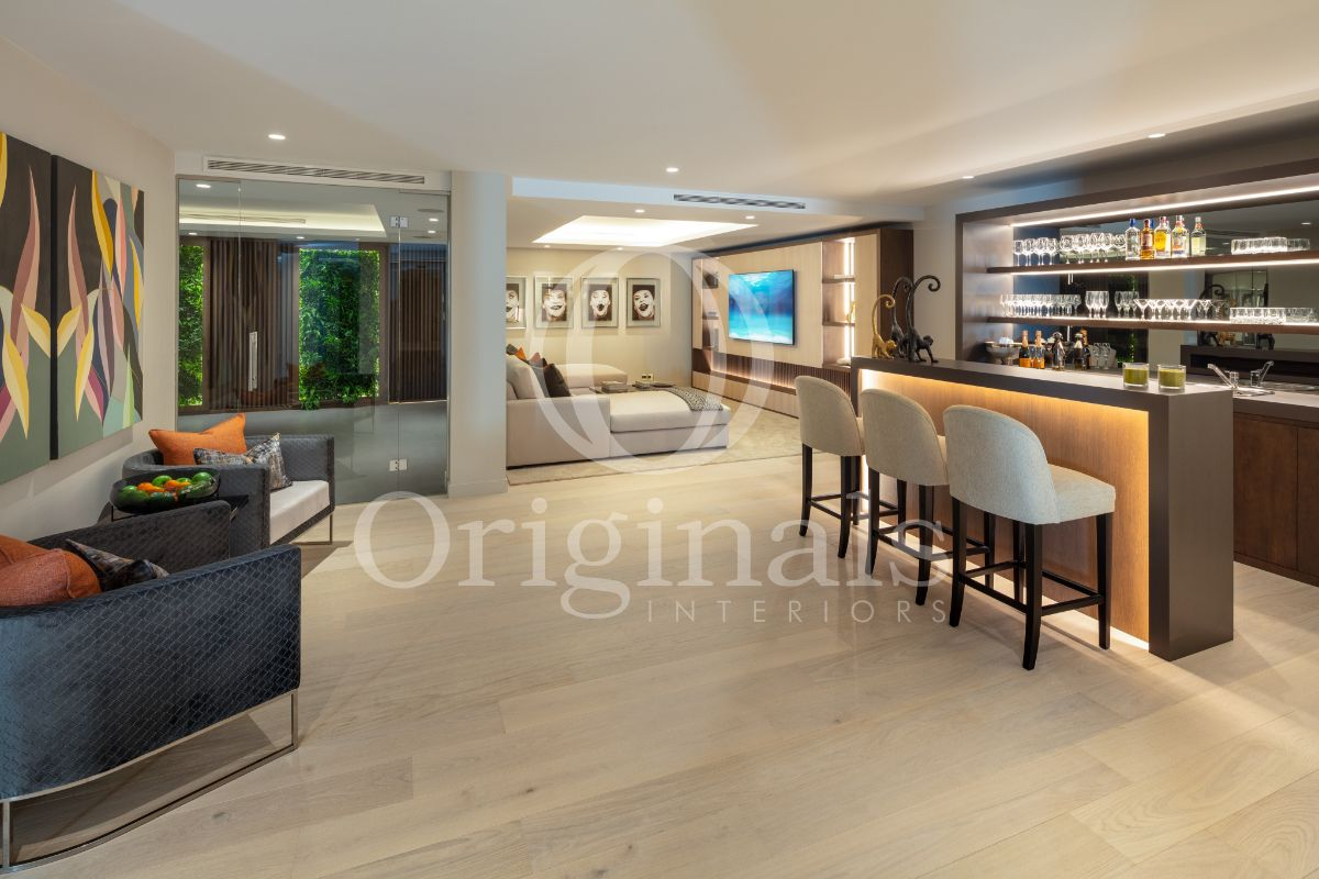 Luxurious grey bar with white bar chair, blue chairs and grey sofa - Originals Interiors