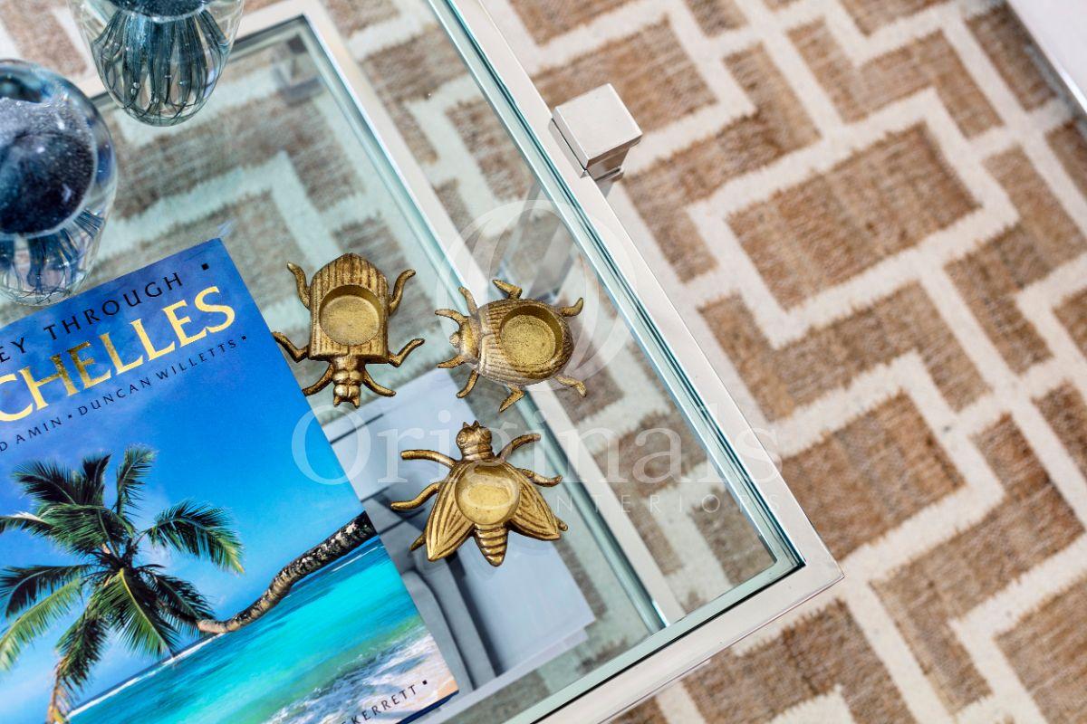 Golden Beetles accessories on glass table - Original Interiors