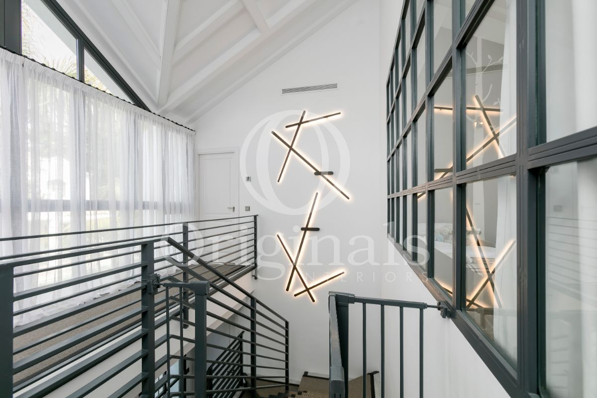 Luxury hallway with black stairs and wall lighting - Originals Interiors