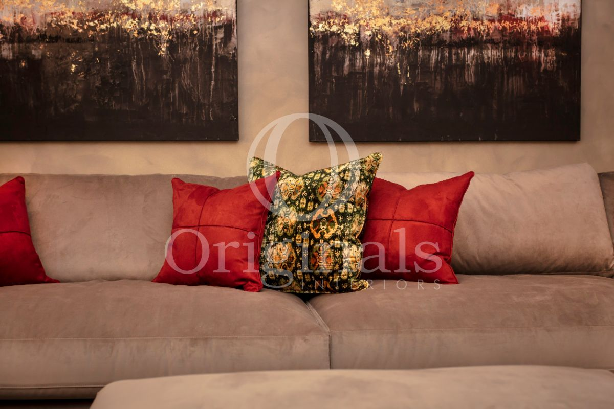 Grey sofa with red pillows and luxury artwork on the wall - Originals Interiors