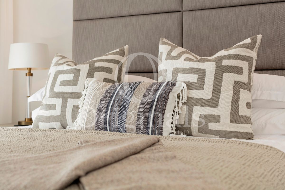 White pillows with brown accents on a luxurious bed - Originals Interiors
