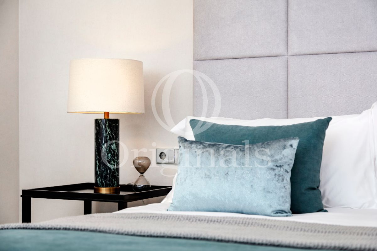 Lamp with turquoise accents and a bed with turquoise sheets and pillows - Originals Interiors