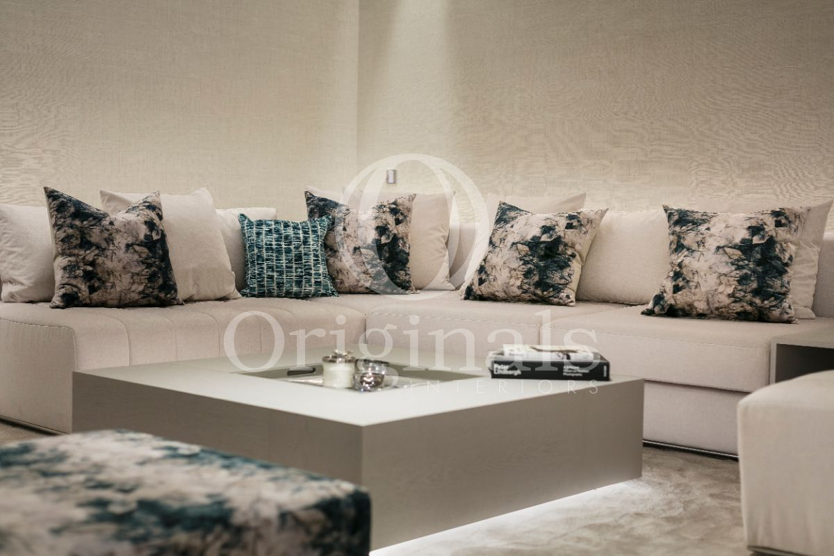 White sofa with white pillows with blue accents and a luxurious coffee table - Originals Interiors