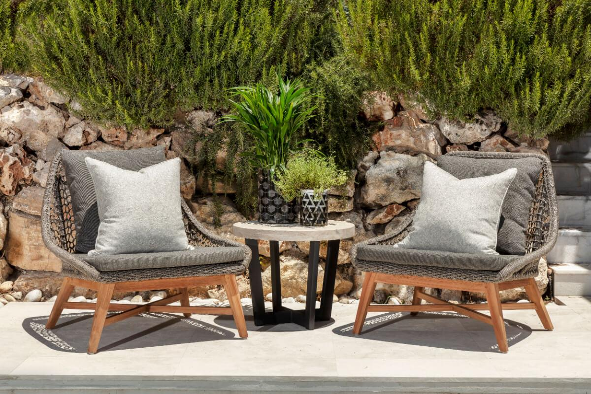 Terrace with plants on the backgorund and black trending chairs designe by Originals Interiors