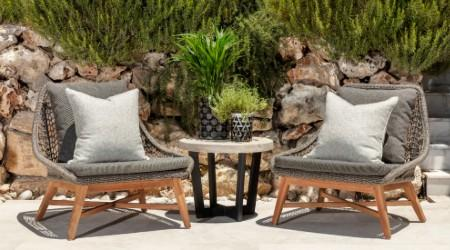 Terrace with plants on the background and black trending chairs designed by Originals Interiors